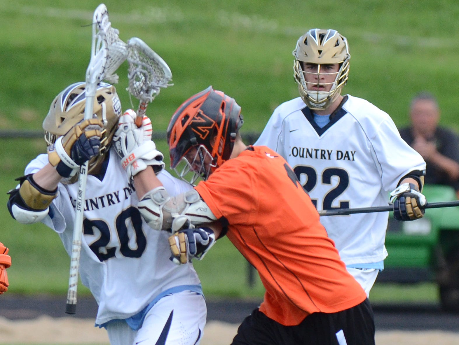 Northville's Harry Dyson (middle) checks Country Day's Cameron Barr during the Division 1-Region 3 boys lacrosse semifinal at Holzer Field.