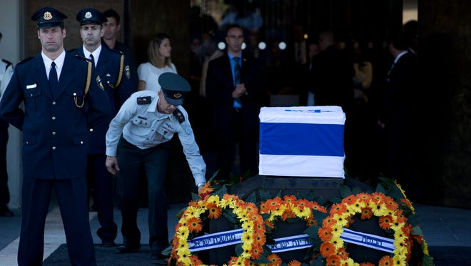 An Israeli army officer lays a wreath as Knesset honor guards stand next to the coffin.