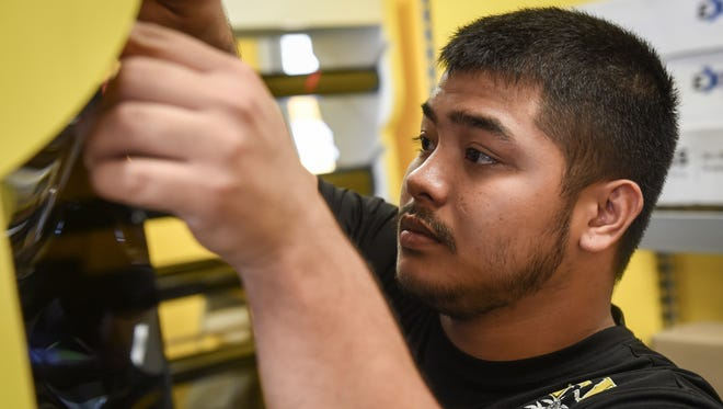 "Thomas San Nicolas selects a length of tint for installation at Island Tinting in East Hagåtña on May 6. After three years of employment and three merit raises, San Nicolas would not appreciate a new hire making an equivalent wage.  ""It would be messed up,"" said San Nicolas."