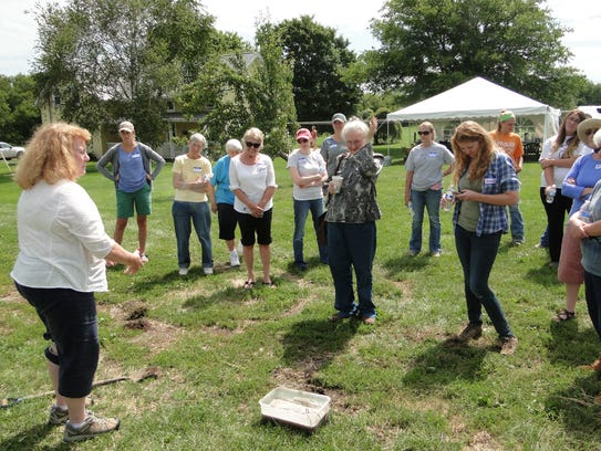 Women gather around to learn more about healthy soil