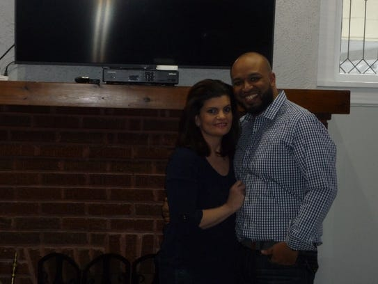 Dana Viri and Ivan Rosa pose by the fireplace of their
