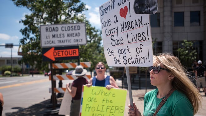 Protesters gathered in Hamilton to share their thoughts on Hamilton Sheriff Jones' policy on Narcan on Saturday July 15, 2017. Sheriff Jones has stated he won't have his deputies using Narcan on overdose victims. Becky Neal, 42, of Hamilton stands with protesters.
