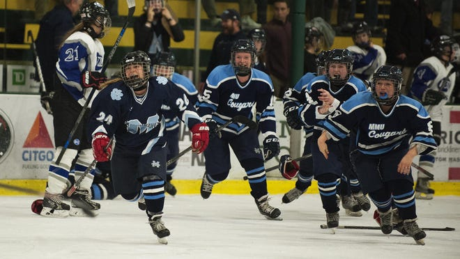 MMU celebrates the championship during the Division II high school girls hockey state championship between the MMU Cougars and the U-32 Raiders at Gutterson Fieldhouse on Wednesday night.