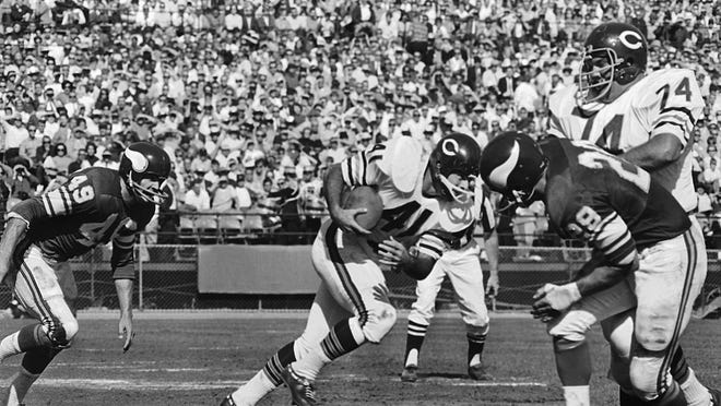 Chicago Bears running back Brian Piccolo charges into Minnesota Viking line after taking handoff from quarterback Jack Concannon in the second quarter of a game in Minneapolis on Sunday, Oct. 1, 1967.