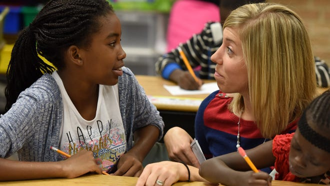 Casey Elder (right) helps Khady Diaw during class at Jane Addams Elementary school.
