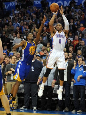 Thunder point guard Russell Westbrook hits a three-pointer to beat the Warriors on Friday.