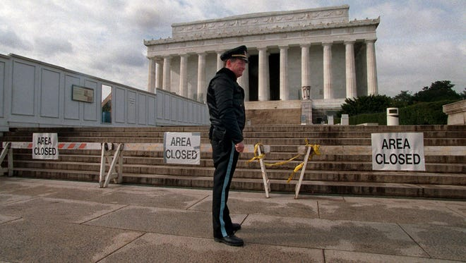 In this Nov. 15, 1995, file photo, a U.S. Park Service police officer stands in front of closed signs at the Lincoln Memorial in Washington, during a partial shutdown of the federal government.