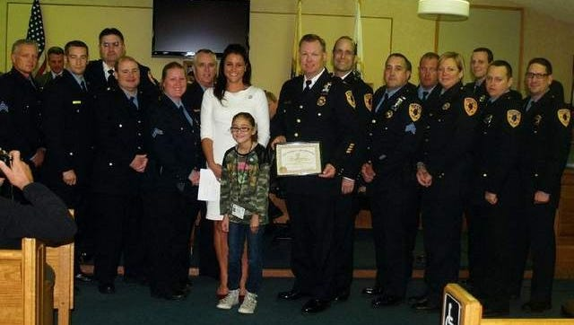 Mayor Stephanie Murray, Mayor For A Day Chloe Davis and Chief Weber are joined by a dozen offers during a presentation annoucning the Police Departments APP Readers Choice Award