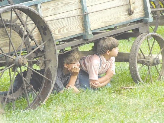 Two Amish boys escape from the rain during the miniature