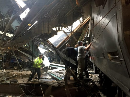 Train personnel inspect the NJ Transit train that crashed
