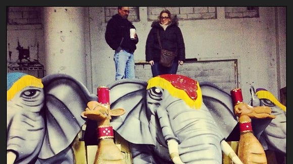 Reporter Carly Q. Romalino and Woodland String Band sax player Rick Tierno stand atop the band's giant elephants, props in the 2014 show.