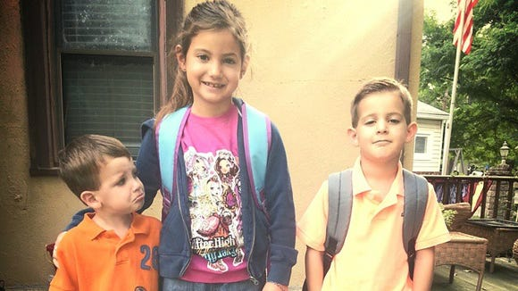 Second-grader Natalee and kindergartner John (right) get ready for school in Brooklawn while brother Ryan, 3, gets ready to miss them.