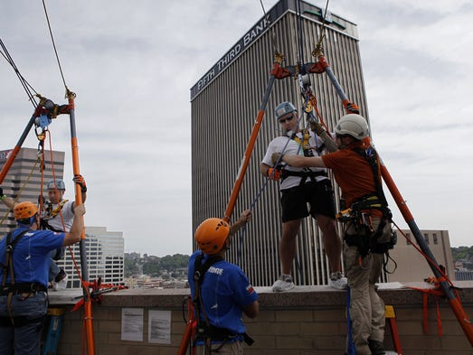 Carl Fries, of Colerain, and Phil Vogel, of Anderson Twp., prepare to rappel down the side of the Westin Cincinnati Hotel Thursday morning during the Shatterproof Challenge. The Shatterproof Challenge is a nationwide charity event to help raise funding and awareness to help fight addiction. Many of those who rappelled are in recovery or rappelling in honor or memory of someone who struggled with addiction.
