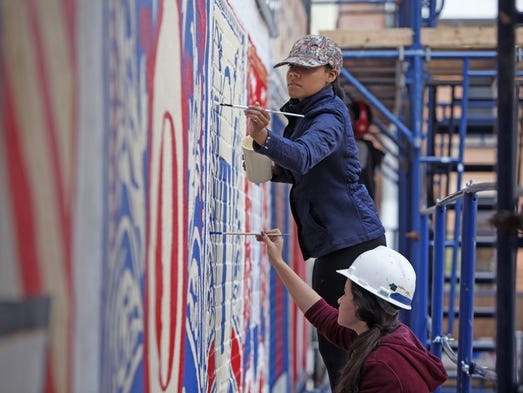 Taylor Helms, front, who will be an Oak Hills senior, and Kimmia Crossty, who will be a sophomore DAAP fashion student at UC, paint the Vine Street Artworks mural of Over-the-Rhine legend Cincinnati Strongman, Henry Holtgrewe.