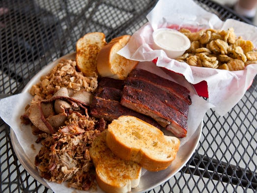 Sampler platter with ribs, brisket, pulled pork, and chicken, plus the fried pickles