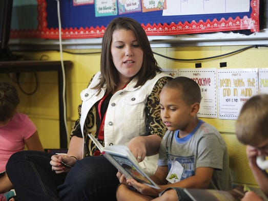 Second grade teacher Ashlie Taylor listens to KaRon McCord read at Cowden Elementary on Wednesday, August 20, 2014.