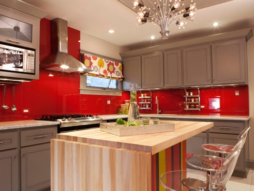 In this photo provided by HGTV, Designer and host of HGTV's Great Rooms, Meg Caswell, painted the walls red then added a clear glass cover to create a chic, vibrant backsplash.  Elements like this, as well as stools, countertop appliances and textiles are great ways to inject color into a kitchen that may have more traditional bones for a look that?s unexpected and modern.