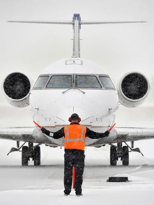 In this file photo a plane is directed into position at the St. Cloud Regional Airport.