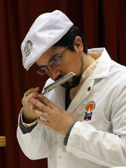 Luis Jimenex Maroto, of Mexico, smells an aged cheddar cheese during the World Championship of Cheese Contest in Madison on March 7, 2018.