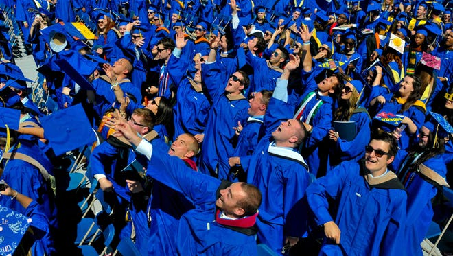 In this May 31, 2014 photo, graduates throw their caps in the air in triumph at the University of Delaware's commencement ceremony in Newark, Del.    (AP Photo/Emily Varisco)