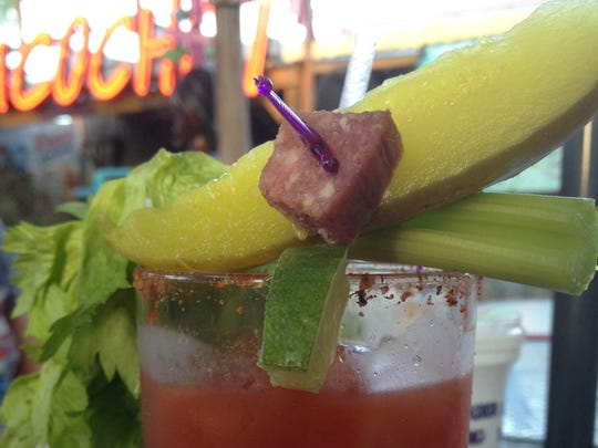 At Redbone's, the Bloody Mary is garnished with smoked sausage, a pickle, celery and lime.