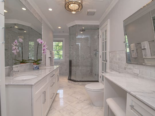 The spa-like master bath features marble floors and counters, a glass-enclosed shower and a jetted tub.