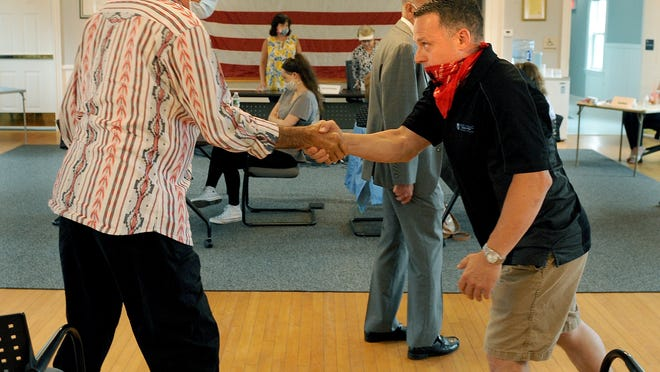 Mendon Board of Selectmen incumbent Lawney Tinio, right, shakes the hand of challenger David Atkinson, after results of a recount were anounced at Town Hall Monday morning.  Tinio, who had originally won by one vote, ended up winning by two votes, 548-546, with four write-ins, and 63 blanks.