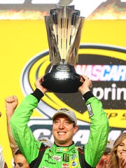 Kyle Busch lifts the Sprint Cup, awarded the winner