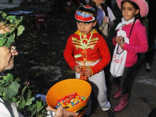 By closing Vermont Avenue to traffic, the community has made room for trick-or-treaters, like this pair, pictured in 2013, the first year the neighborhood closed the road.