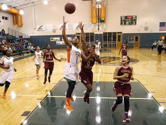FAMU DRS seventh grader Erin Turral lays the ball up past Florida High's Auryn West during their game at FAMU DRS on Saturday. Turral scored 21 points in a 72-47 win.