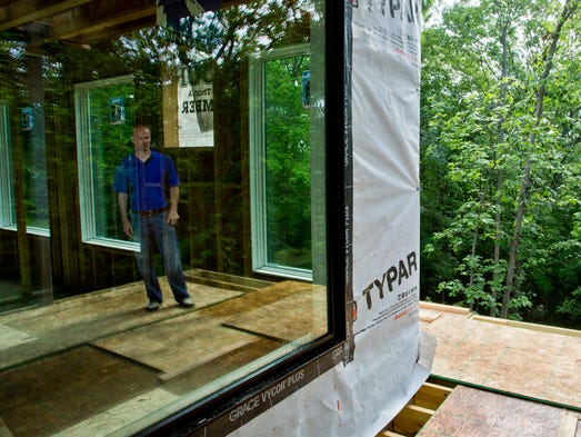 Chuck Hockema is reflected in a window on one of the decks of the new home he is building on Happy Hollow Road Monday, June 16, 2014, in West Lafayette. The home will be over 4,000 square feet.