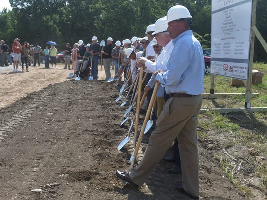 Yellville Mayor Shawn Lane (foreground) prepares to break ground Friday on Marion County's new jail and law enforcement facility.