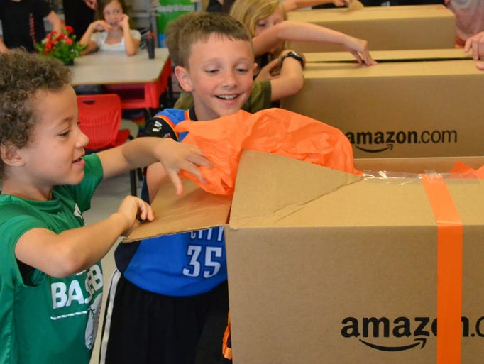 First-graders at Thornwilde Elementary School open boxes filled with 40 Kindle Fire HD Devices and $2,500 content gift cards donated by Amazon Fulfillment to the Boone County school district.