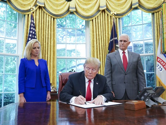 Homeland Security Secretary Kirstjen Nielsen and Vice President Mike Pence look on as President Donald Trump signs an executive order aimed at putting an end to the controversial separation of migrant families at the border.