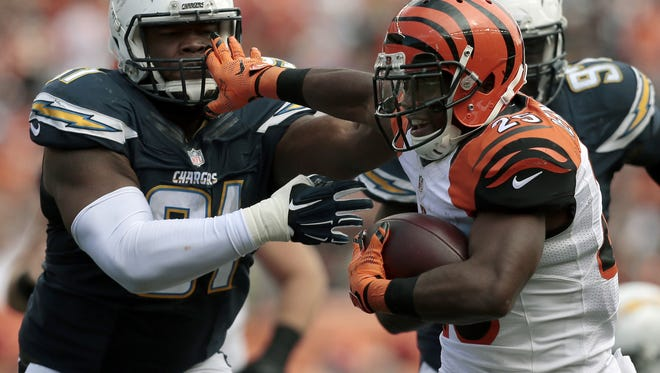 Cincinnati Bengals running back Giovani Bernard (25) stiff arms San Diego Chargers defensive end Kendall Reyes (91) on a carry in the fourth quarter of the NFL football game between the Cincinnati Bengals and the San Diego Chargers at Paul Brown Stadium on Sunday, Sept. 20, 2015. The Bengals won 24-19 in the home opener, improving to 2-0.