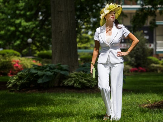 Tanyell Dell'Oso poses in a lawn green hat with cream colored French ribbon and an ostrich feather purchased at Touche' Accessories in King of Prussia; a classic White House Black Market short sleeved cream pant suit; a Franco Sarto cream peep-toe wedge shoe; a pearl necklace and earring set with diamond, ruby and pearl brooch and Tori Burch green leather wristlet near the paddocks at Delaware Park on Wednesday afternoon.