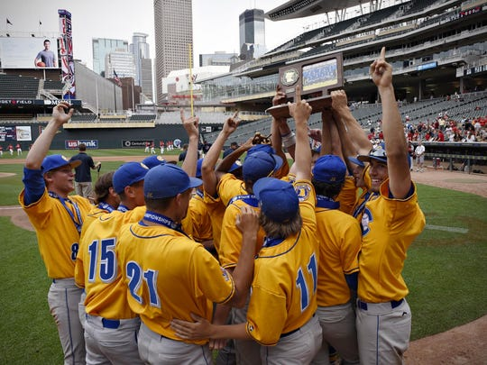 Cathedral players hold up the trophy for the fans after beating Minnehaha Academy for the Class 2A championship title Monday, June 15, 2015, at Target Field. Cathedral beat Minnehaha Academy 10-1.