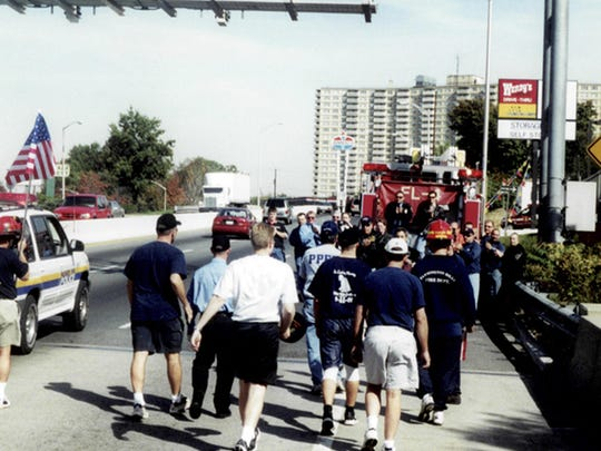 This 2001 photo provided by Larry Gauthier shows members of southeastern Michigan's firefighting community taking part in a 755-mile walk to commemorate the bravery and sacrifice of the first responders who assisted victims of the Sept. 11, 2001, terror attacks. The trek took place about a month after the attacks. It began at the Ambassador Bridge in Detroit and ended at the Brooklyn Bridge. (Larry Gauthier via AP)