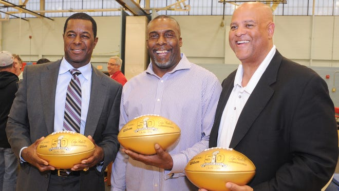 Former NFL players and Pennsauken grads Dwight Hicks, John Taylor and Billy Griggs pose for a picture with commemorative gold footballs presented to the school horning Super Bowl 50 on Friday. 5.13.16.
