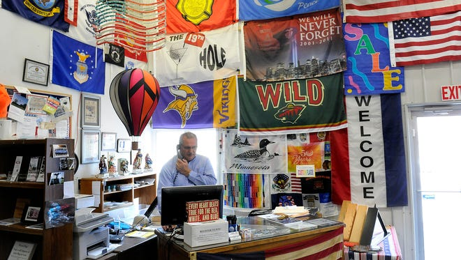 Tim Coil answers the phone at Coil's Flags, Flagpoles and Custom Embroidery on April 15 in St. Cloud.