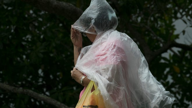Janette Garay tries to stay dry before a heavy rain comes into downtown Fort Myers on Wednesday June 7, 2017.