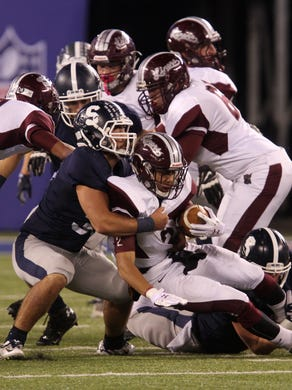 Middletown South's Dylan Rogers tackles Phillipsburg's #2 Jaquan Jones in the first quarter during the North 2 Group IV game of the 2015 NJSIAA/MetLife Stadium High School Football Championships at MetLife Stadium in East Rutherford, NJ Saturday December 5, 2015.