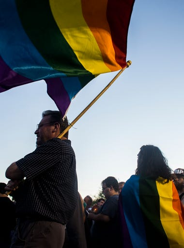 Alex Oliphant holds a rainbow flag outside Phoenix Pride during a vigil for the victims of the Orlando shooting on June 12, 2016 in Phoenix, Ariz.