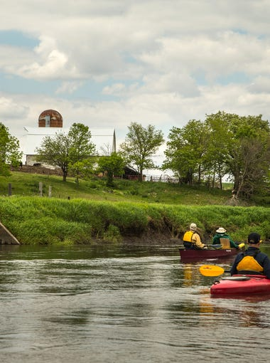 Rex Harvey and Steve Roe paddle past a farm as they head down the Raccoon River with a group of friends in Sac County Thursday, May 19, 2016.