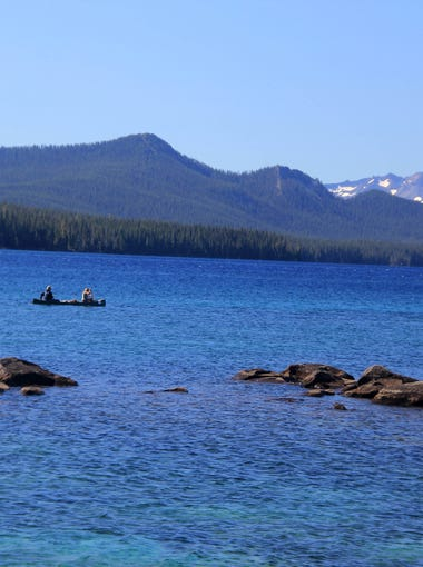 A canoe slides across the surface of Waldo Lake.