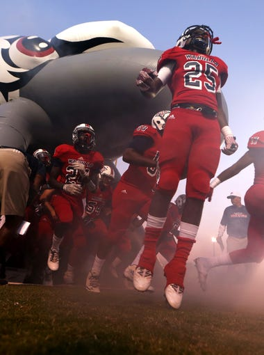 Wakulla's players run out on to the field before their game against Godby in Crawfordville on Friday.