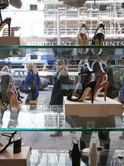 People walk past high heels on display in a shoe store