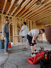 In this Friday, March 24, 2017, photo, Zach Tyson, left, owner of Tyson Construction, talks to electricians in a home he is constructing in Destrahan, La. General contractors and other small businesses in the remodeling industry can look forward to strong growth in the coming years, but the big force behind that business may be surprising: baby boomers. Tyson estimates that between 30 percent and 40 percent of his revenue is coming from boomer renovations, up from 15 percent to 20 percent five years ago. (AP Photo/Gerald Herbert)