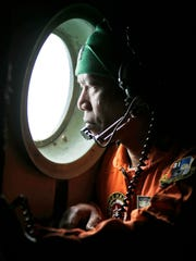 A crew of an Indonesian Air Force C-130 airplane of the 31st Air Squadron looks out of the window during a search operation for the missing AirAsia flight 8501 jetliner over the waters of Karimata Strait in Indonesia, Monday, Dec. 29, 2014.