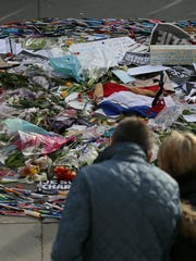 People look at a collection of pens and tributes during